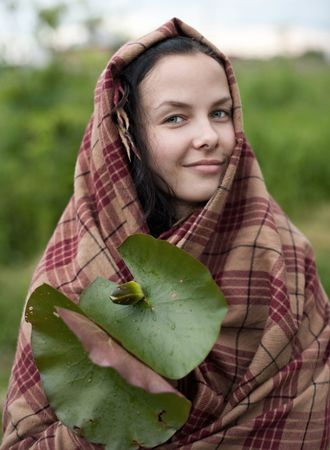 Young beautiful woman wrapped in a plaid holding a water lily, outdoors Stock Photo - 8186269