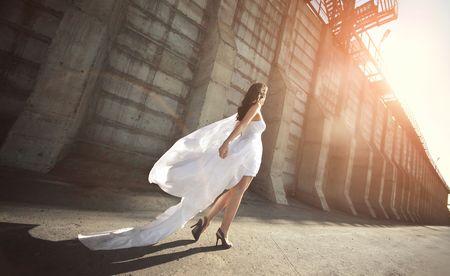 Beutiful bride in wedding dress walking down the street Stock Photo