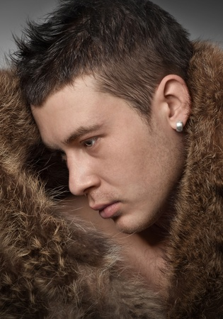 Close-up of  handsome  young man wearing in fur coat photo