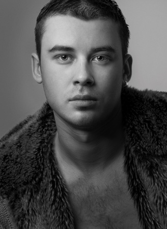 ccloseup: Portrait of  handsome  young man wearing in fur coat (black & white) Stock Photo