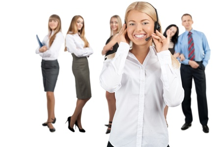 headset business: Portrait of a pretty female call center employee with colleagues standing in the background