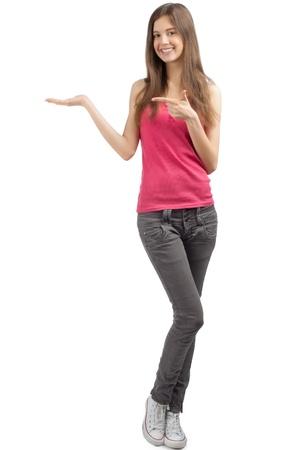 happy young: Retrato de una ni�a feliz ocasional que muestra algo en la palma de la mano y se�alando, contra el fondo blanco