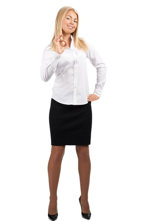 all smiles: Full length portrait of confident young businesswoman showing OK sign and smiling, over white background