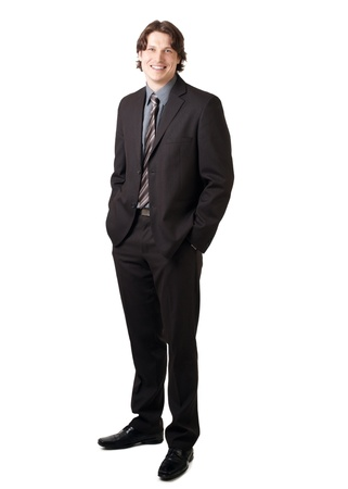 25 to 30: Full length portrait of a young confident businessman standing with hands in the pockets and smiling Stock Photo