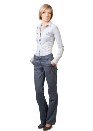 Full length portrait of confident  blond businesswoman standing with hands in pockets against white background