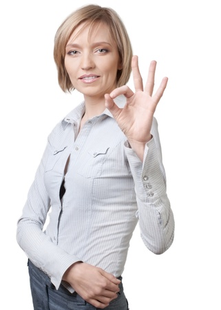 ok sign: Smiling blond businesswoman showing ok sign over white background Stock Photo