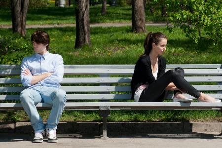 desconfianza: Pareja joven en la pelea sentado en el banco en el parque Foto de archivo