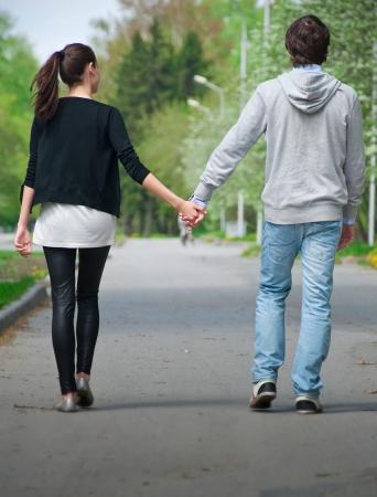 romantico: Pareja joven caminando juntos mano a mano en el parque, vista trasera