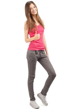 Full length portrait of a happy young woman standing and showing thumbs up, against white background Stock Photo - 10821680