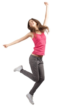arm extended: Full length studio shot of happy young woman jumping with arms extended . Over white background