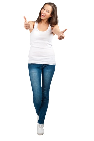 Full length portrait of a happy young woman standing and showing thumbs up, against white background photo