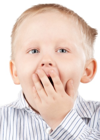 concept images: Portrait of surprised little boy with blond hair covering his mouth by his hand