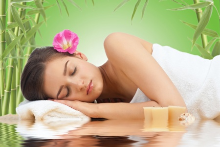Portrait of young beautiful spa woman with flower in her hair lying and relaxing photo