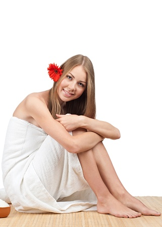 Young beautiful spa woman with flower in her hair sitting on bamboo mat at spa salon Stock Photo - 10827797