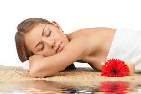 Portrait of young beautiful spa woman with closed eyes lying on bamboo mat in water photo
