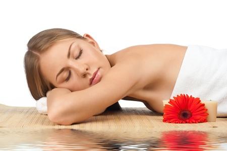 closed eyes: Portret van jonge mooie spa vrouw met gesloten ogen liggen op bamboe mat in het water