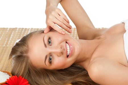 Portrait of young beautiful spa woman with flower lying on bamboo mat at spa salon Stock Photo - 10827707