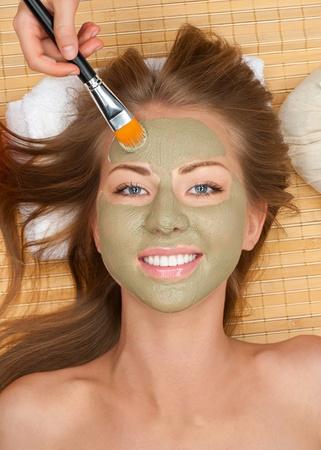 pulizia viso: Primo piano di giovane donna bella con maschera viso di argilla presso il salone spa