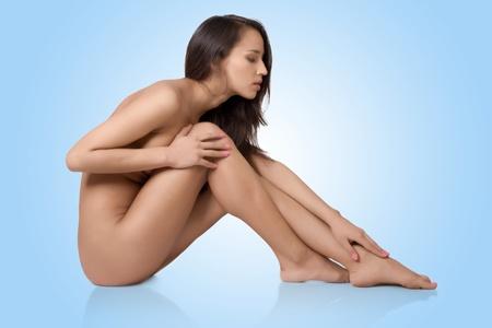 nackt: Nackte sch�ne Frau mit langen braunen Haaren und nat�rliches Make-up, auf blauem isoliert