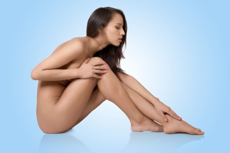 Naked beautyful woman with long brown hair and natural make-up, isolated on blue Stock Photo