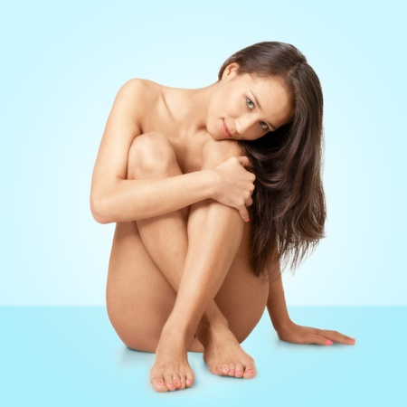 20s naked: Naked beautyful woman with long brown hair sitting and smiling, isolated on blue