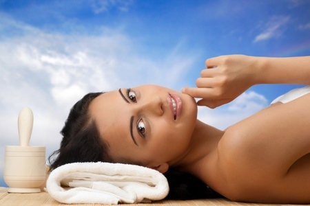 bare body women: Young beautiful woman lying on bamboo mat at spa salon. Against blue sky