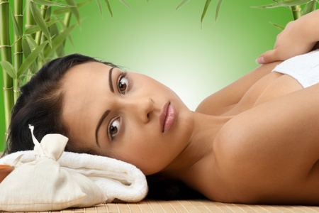 Portrait of young beautiful spa woman lying on bamboo mat and smiling. Against green bamboo background. photo