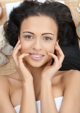 bare body women: Close-up portrait of young beautiful spa woman lying on bamboo mat at spa salon and smiling Stock Photo