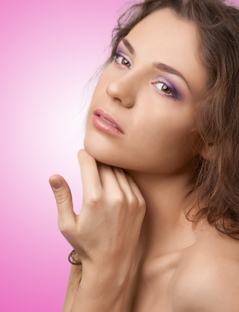 Attractive female with make-up touching her face and looking away, over pink background Stock Photo - 10828266