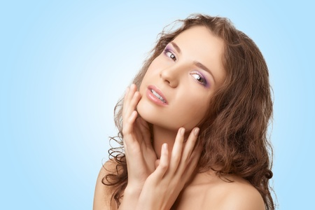 Attractive female with perfect skin and curly hair touching her face, over blue background Stock Photo - 10841449