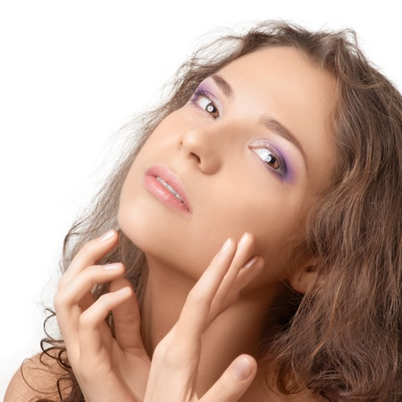 Attractive female with make-up touching her face and looking away, over white background Stock Photo - 10841457