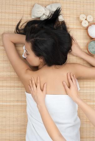 Beautiful young woman getting a massage  lying on bamboo mat at spa salon photo