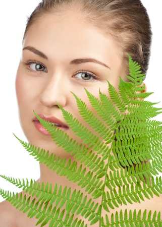 Closeup portrait of young beautiful woman with green leaf, over white background Stock Photo - 10841212