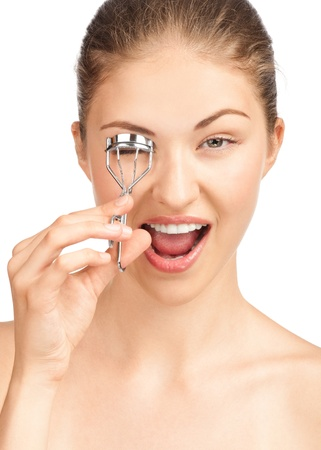 Portrait of cheerful beautiful woman making curl eyelashes using curling cosmetic tool. Over white background photo