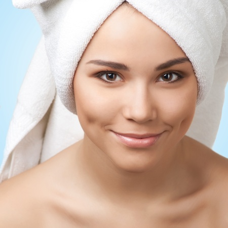 Close-up of a pretty girl wearing towel on head smiling and looking at camera, isolated on blue photo