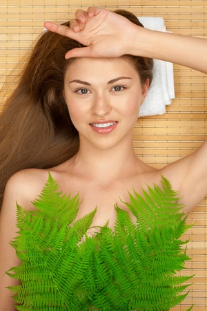 Portrait of young beautiful woman with green leaf lying on bamboo mat at spa salon photo