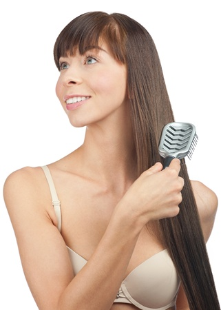 Portrait of young beautiful woman brushing her long straight healthy hair photo