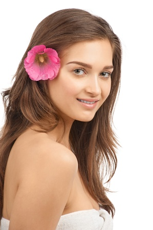 Portrait of young beautiful spa woman with pink flower in her hair. Isolated on white background photo