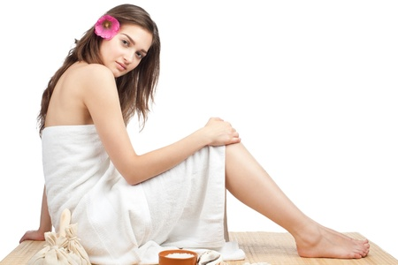 Portrait of young beautiful spa woman sitting on bamboo mat at spa salon Stock Photo - 10841554
