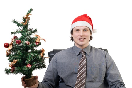 Smiling businessman in a Santas hat holding a small Christmas tree in his hand photo
