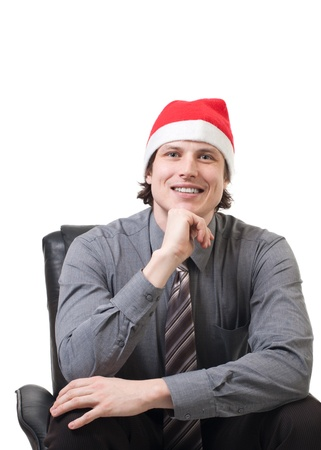 Handsome businessman in a Santa hat sitting in a armchair over white background photo