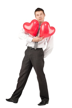 Handsome young man with two red heart-like balloons, isolated on white photo