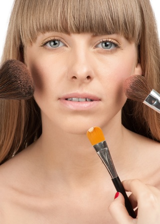 Makeup artist applying makeup on beautiful young womans face, isolated on white photo