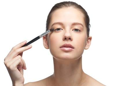 Close-up portrait of young beautiful woman applying makeup, isolated on white background photo