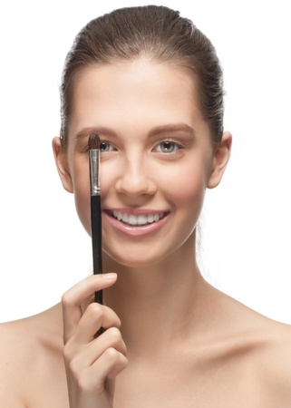 Close-up portrait of beautiful girl with brush for makeup smiling, isolated on white background photo