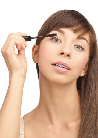 Beautiful woman applying mascara on her eyelashes, isolated on white background Stock Photo - 10841295