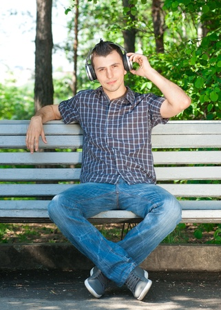 Portrait of a relaxed young man sitting on bench in park and listening to music on headphone  Stock Photo - 10842712