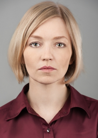 Close up portrait of a pretty young blond woman with serious face  Stock Photo
