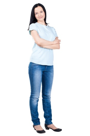 jeans woman: Full length portrait of a happy young female standing with folded hand against white background Stock Photo