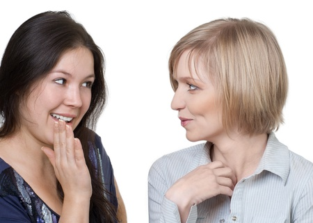 two happy young girlfriends talking aginst white background photo